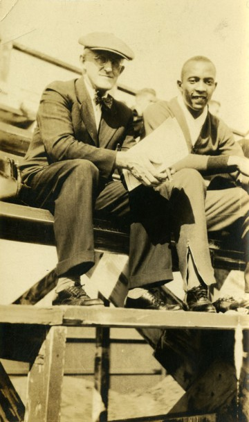 Jesse Owens sitting with Coach Charles Riley on bleachers, 1934
